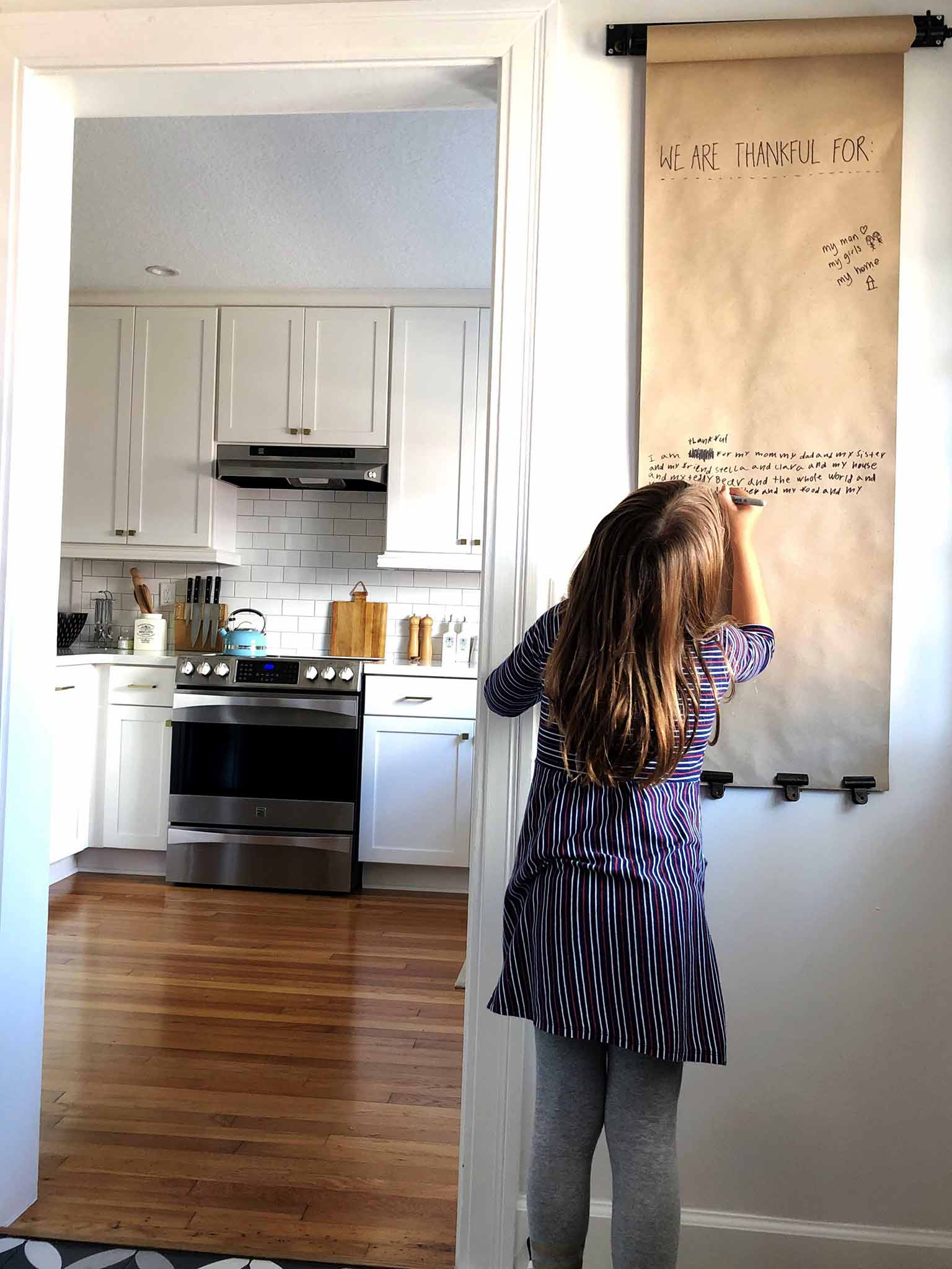 Kids using hanging note roll - Covering up an electrical panel - That Homebird Life Blog