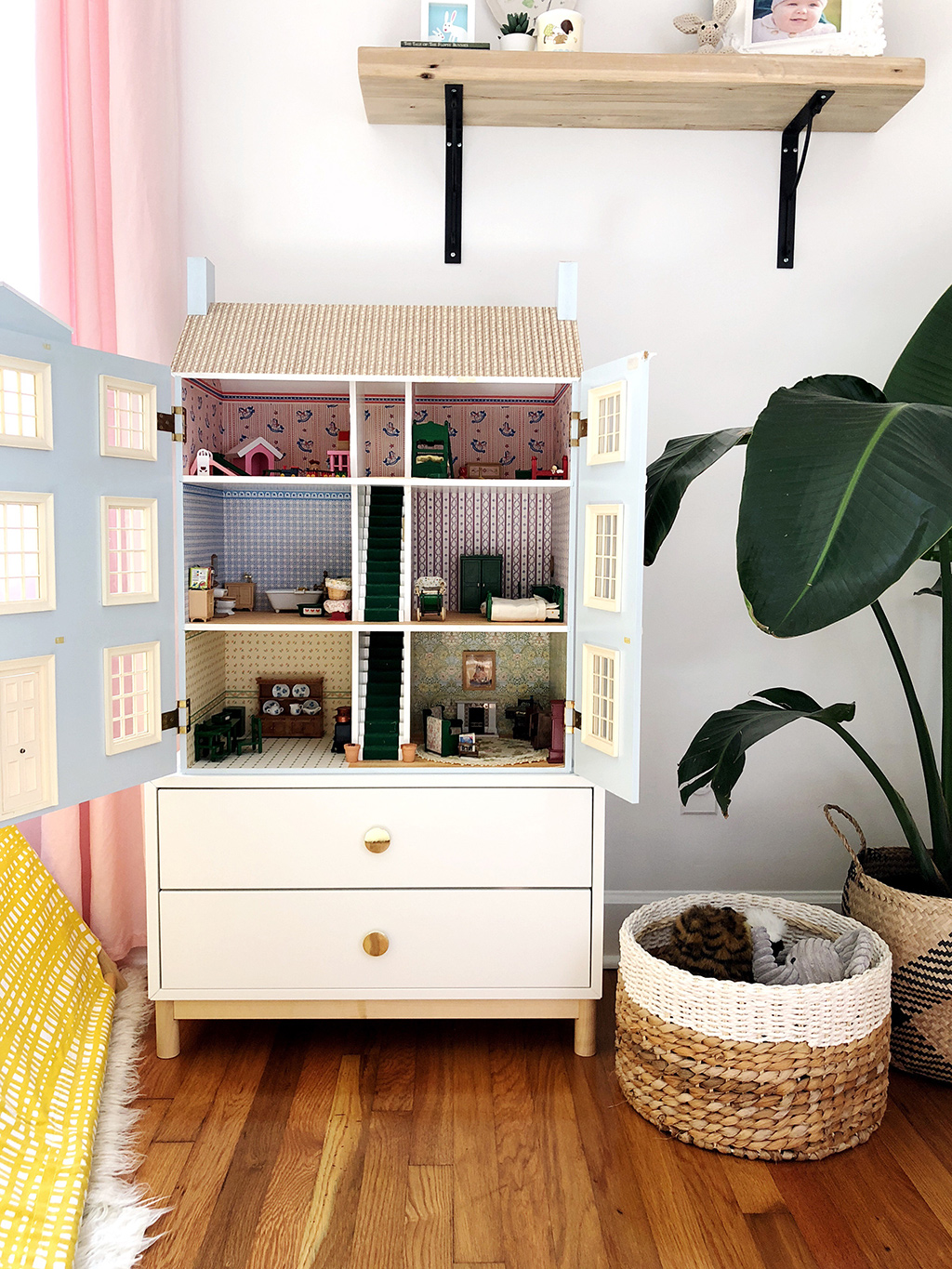 blue doll house in corner of girls bedroom