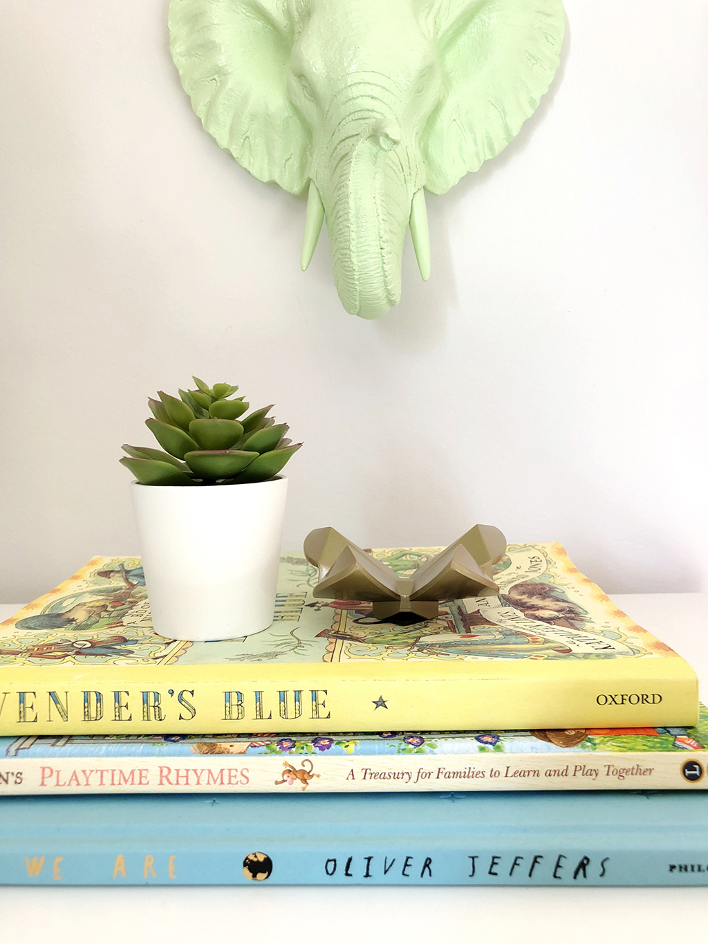 stack of books with faux plant