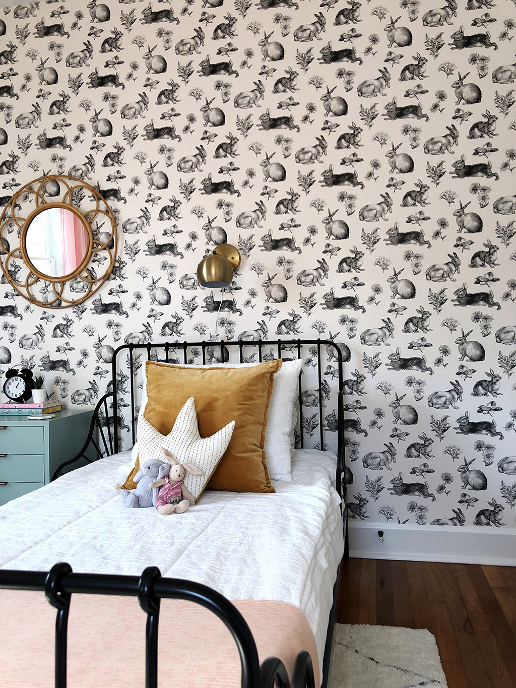 twin bed with white bedding and rabbit wallpaper