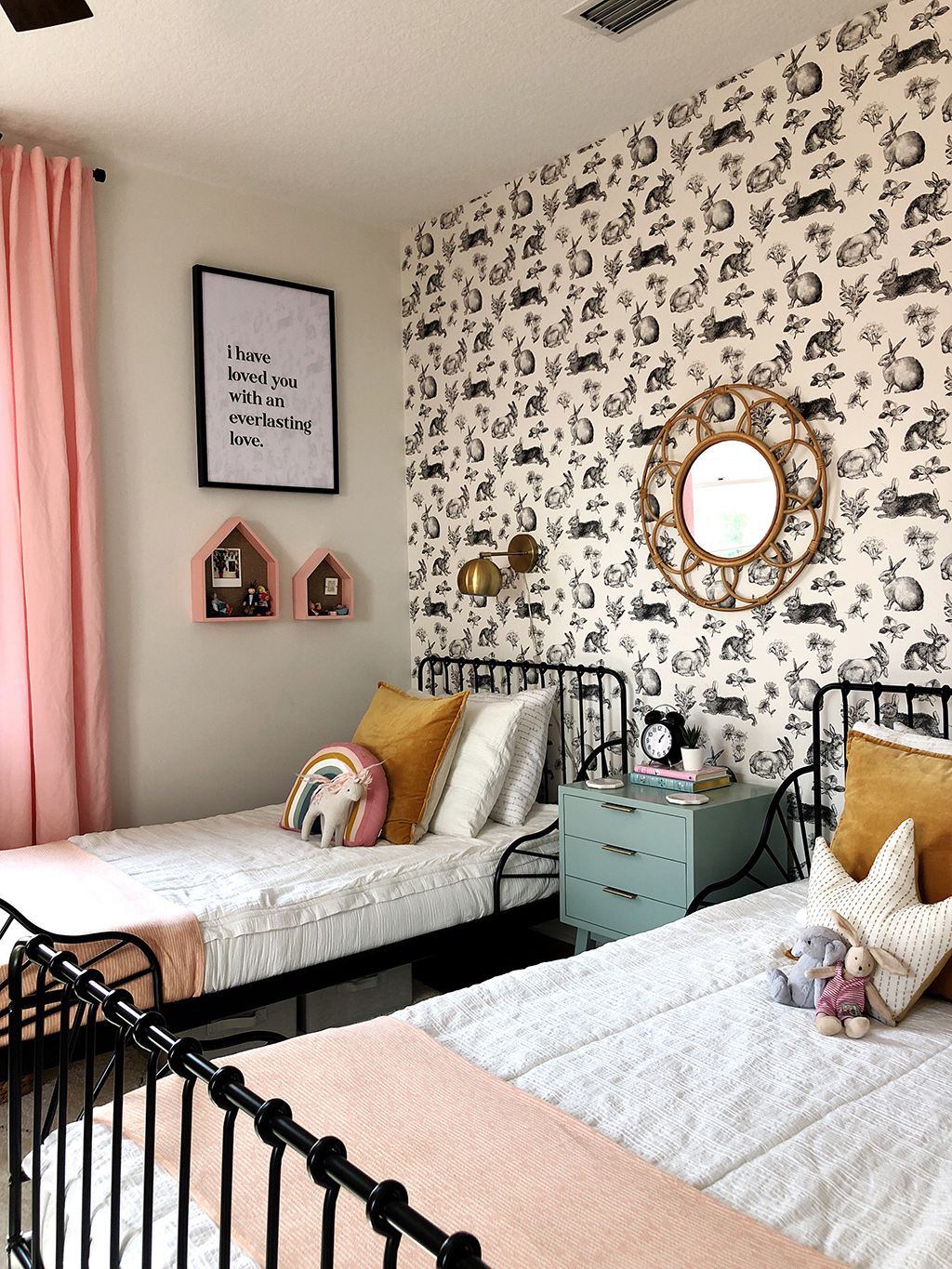 twin beds with white bedding and rabbit wallpaper