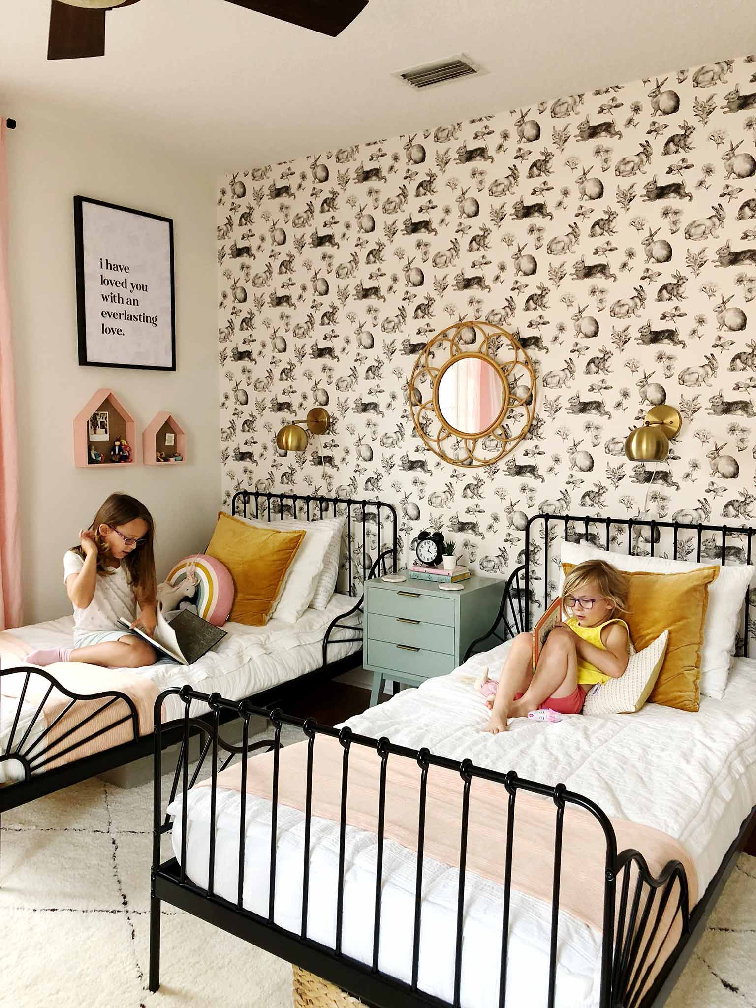 shared girls' bedroom with twin beds and rabbit wallpaper