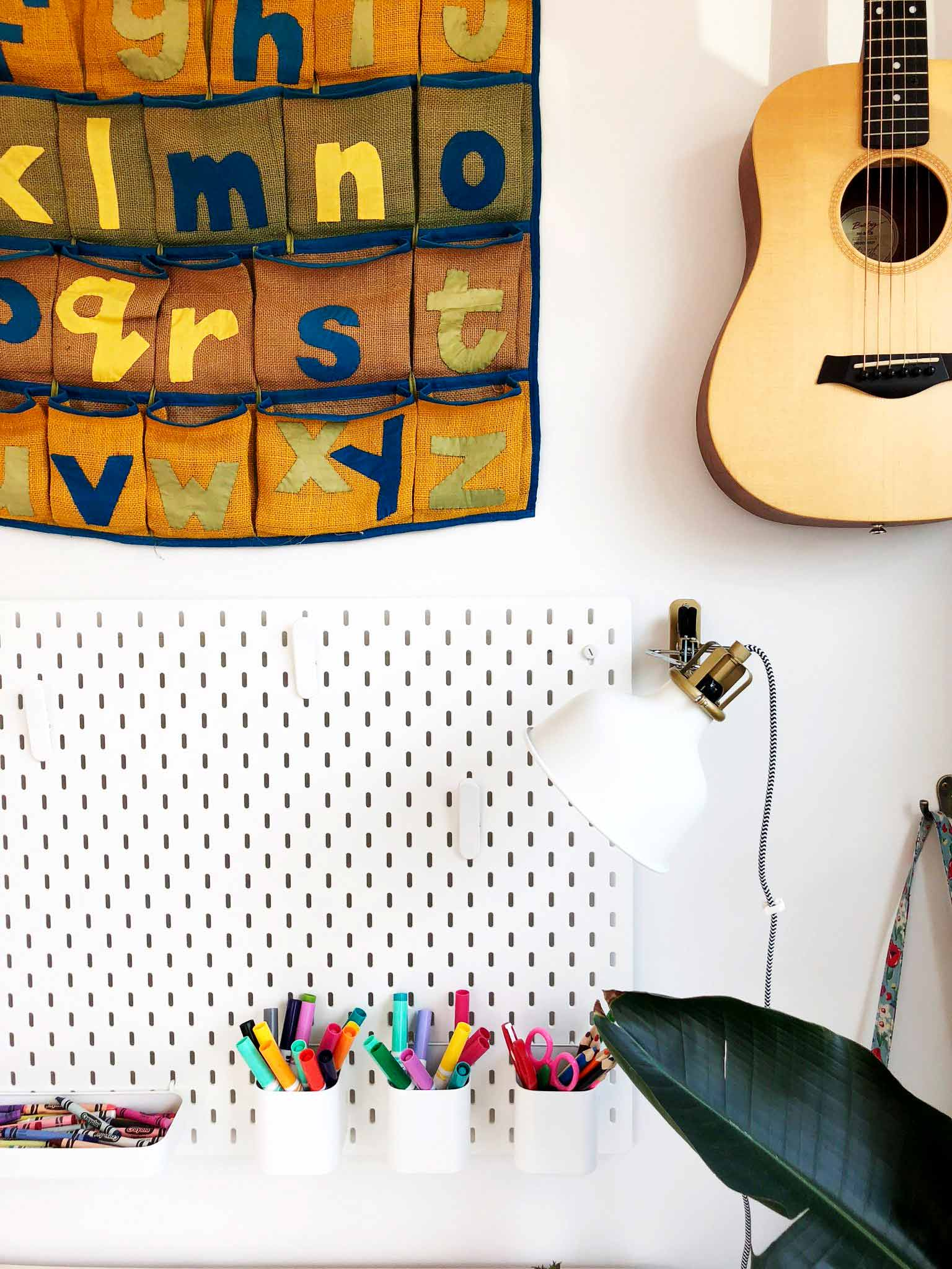 IKEA SKADIS pegboard with pens and crayons, guitar mounted on the wall