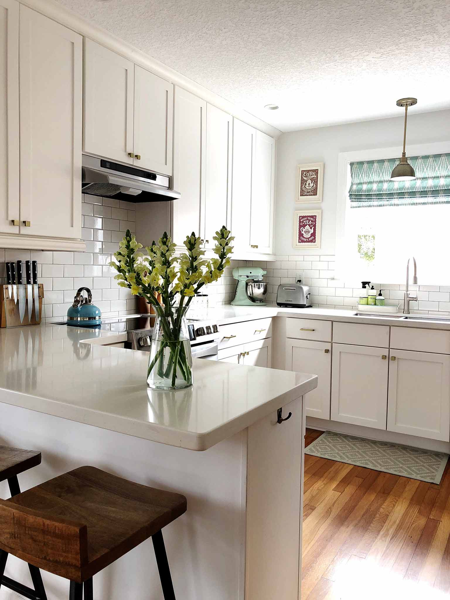 Clean white kitchen with vase of flowers on the penisular