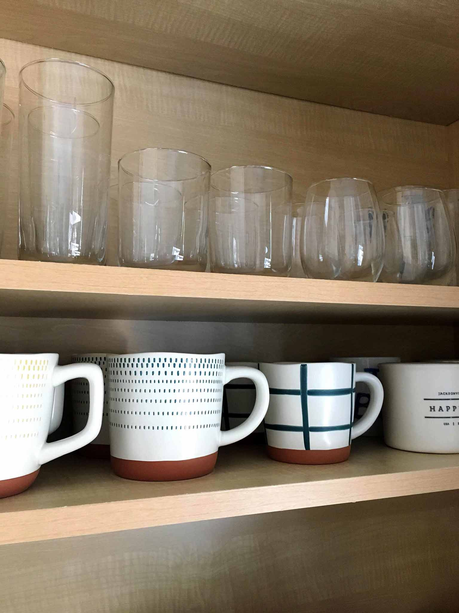 coffee mugs and glasses in kitchen cabinet