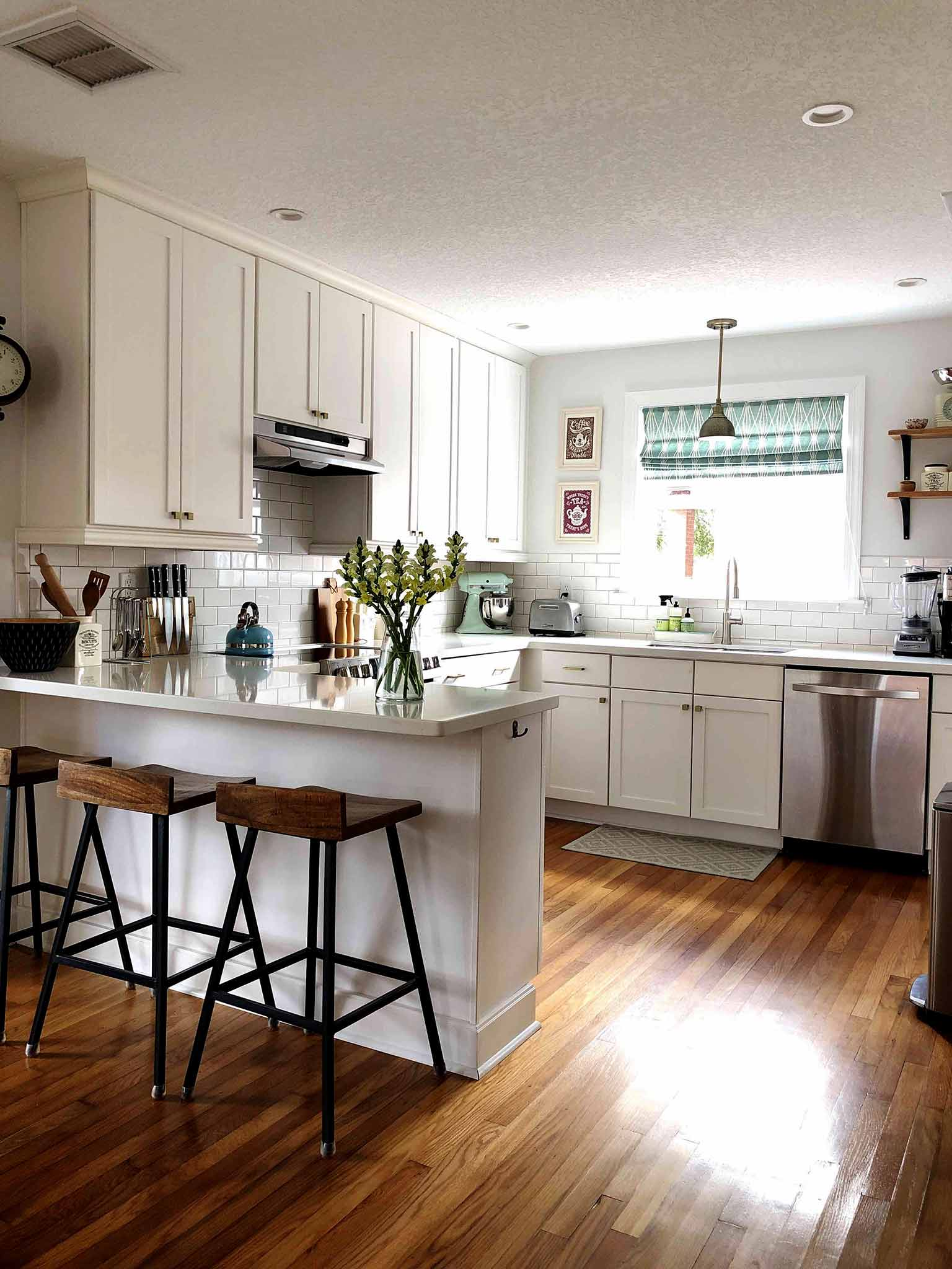 open concept kitchen with white cabinets, white subway tile and hardwood floors