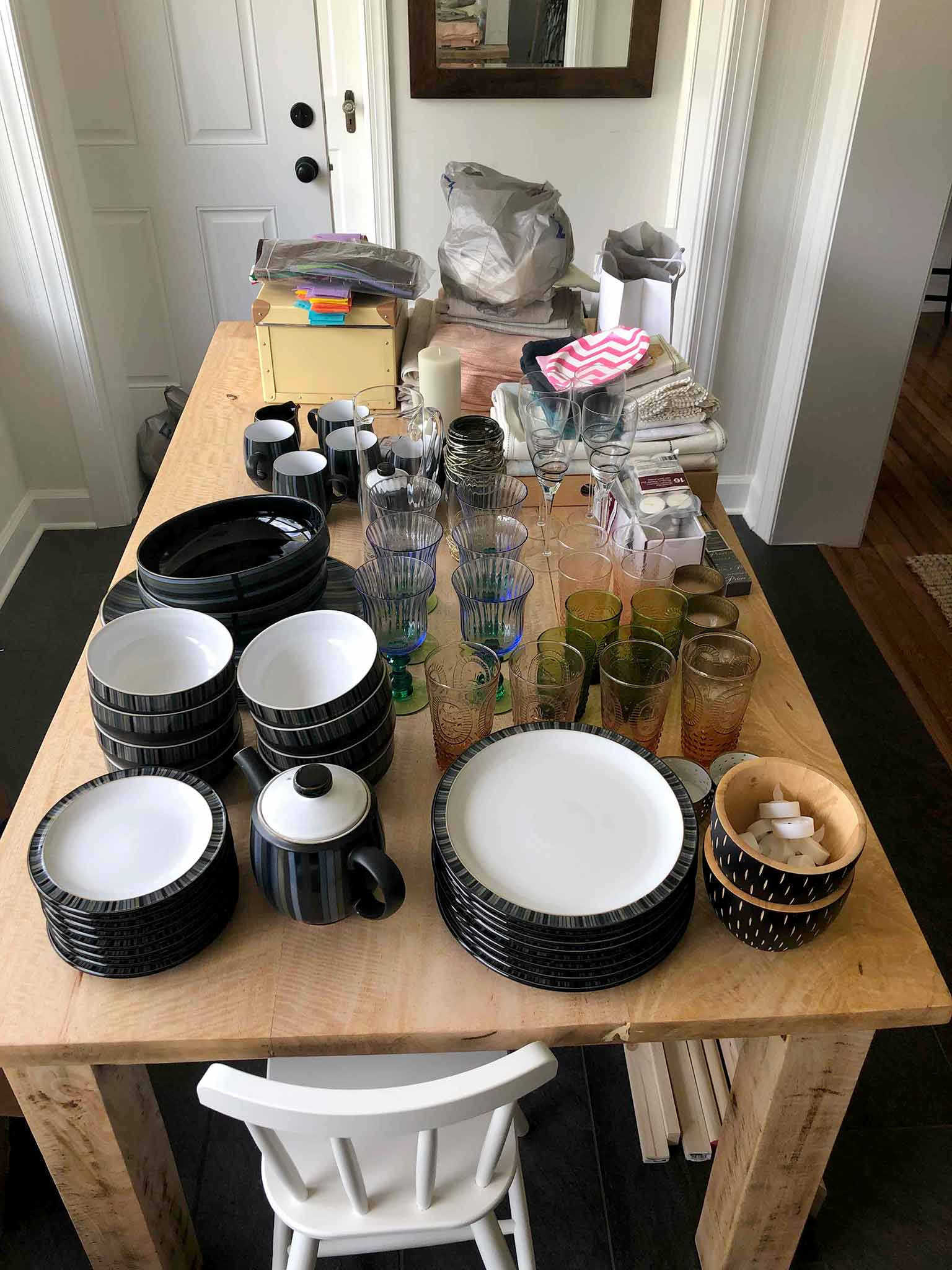 Dining table piled with glassware and dishes