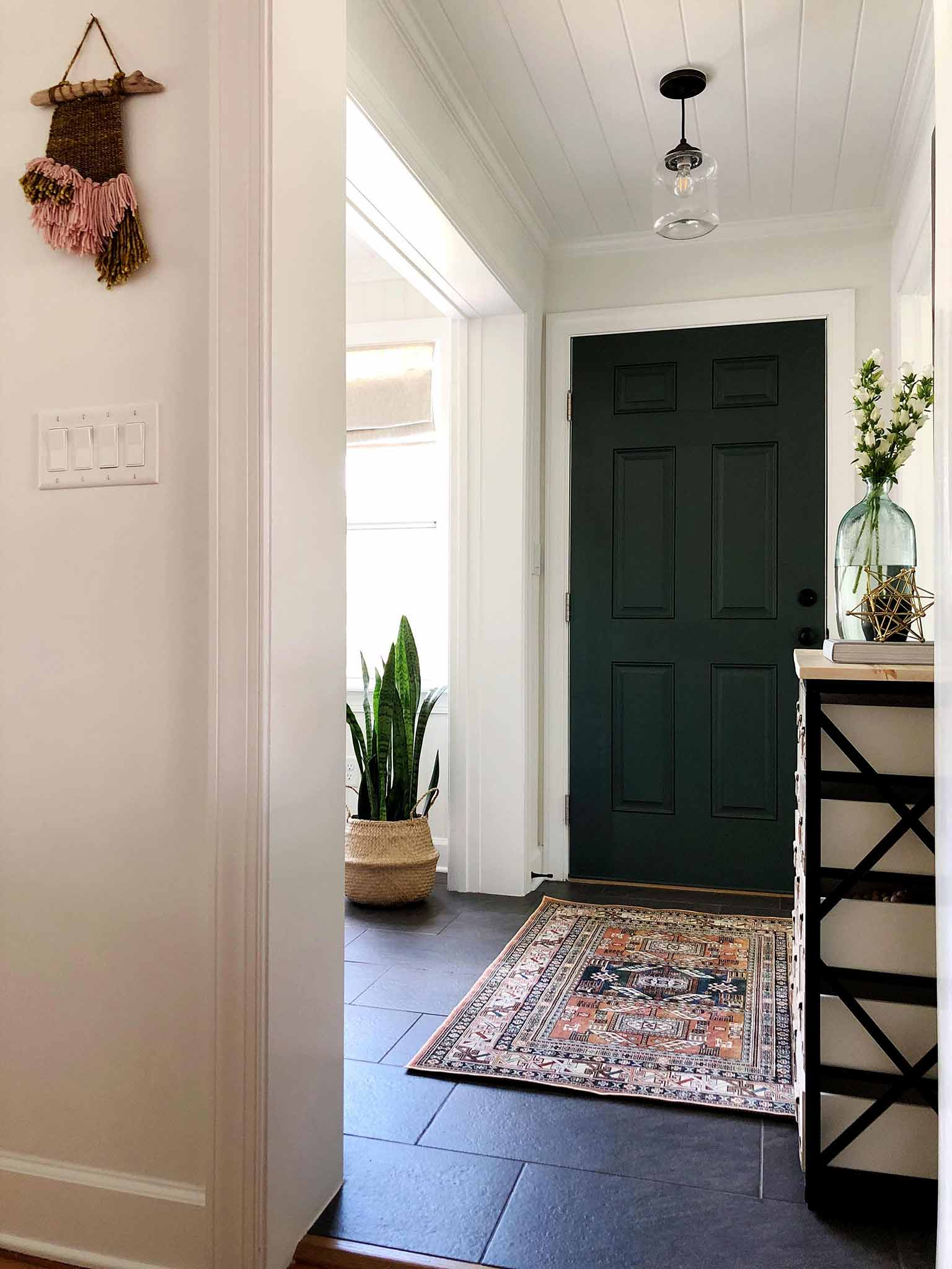 entryway with dark green door and patterned rug