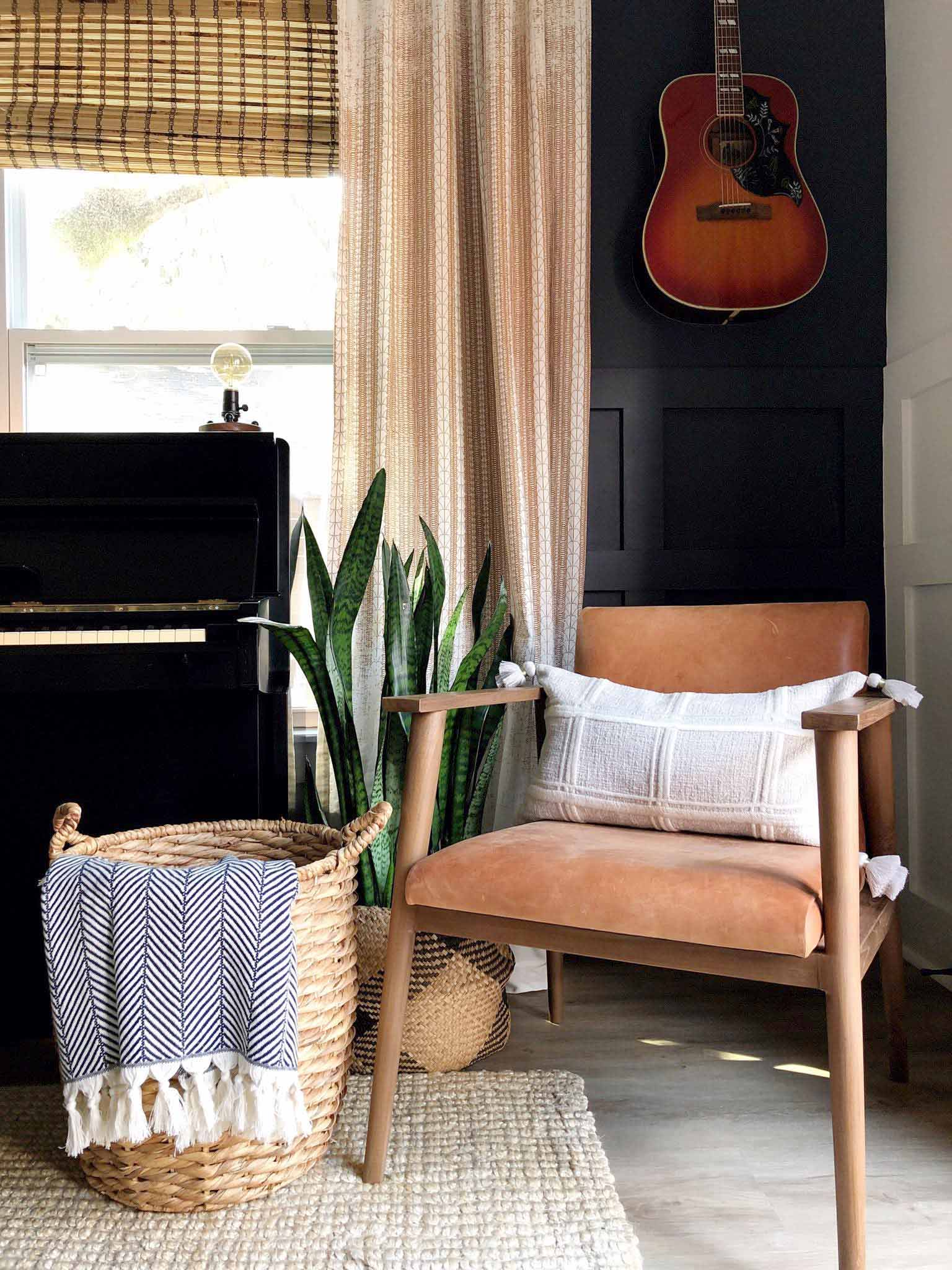 chair in corner with guitar on the wall