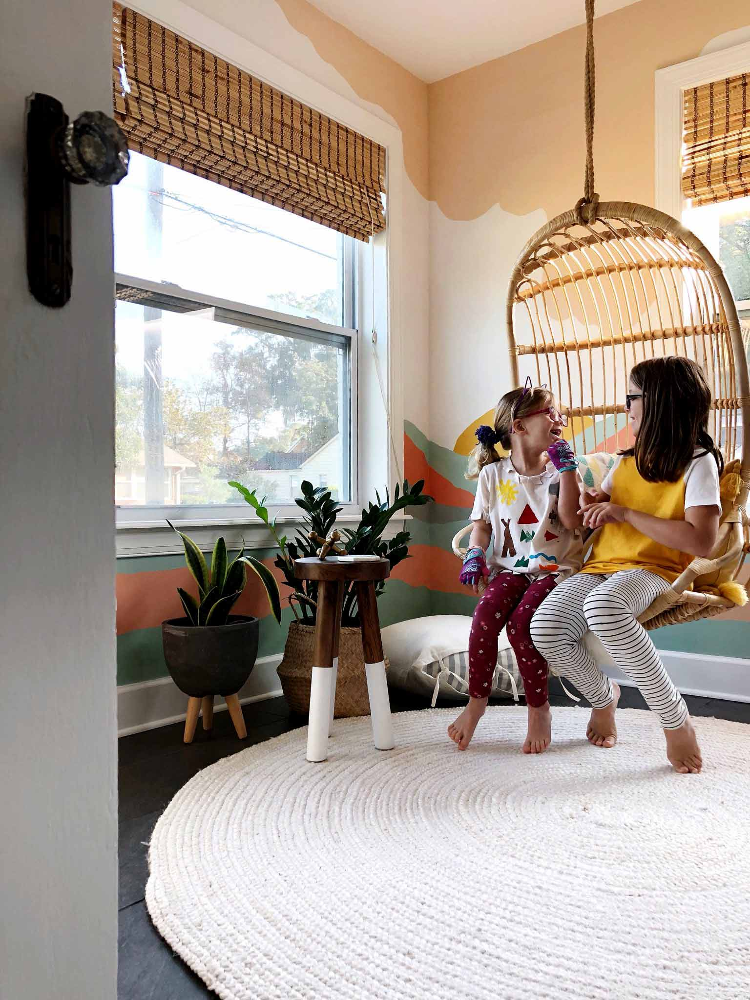 playroom with colorful mural and two girls in hanging chair