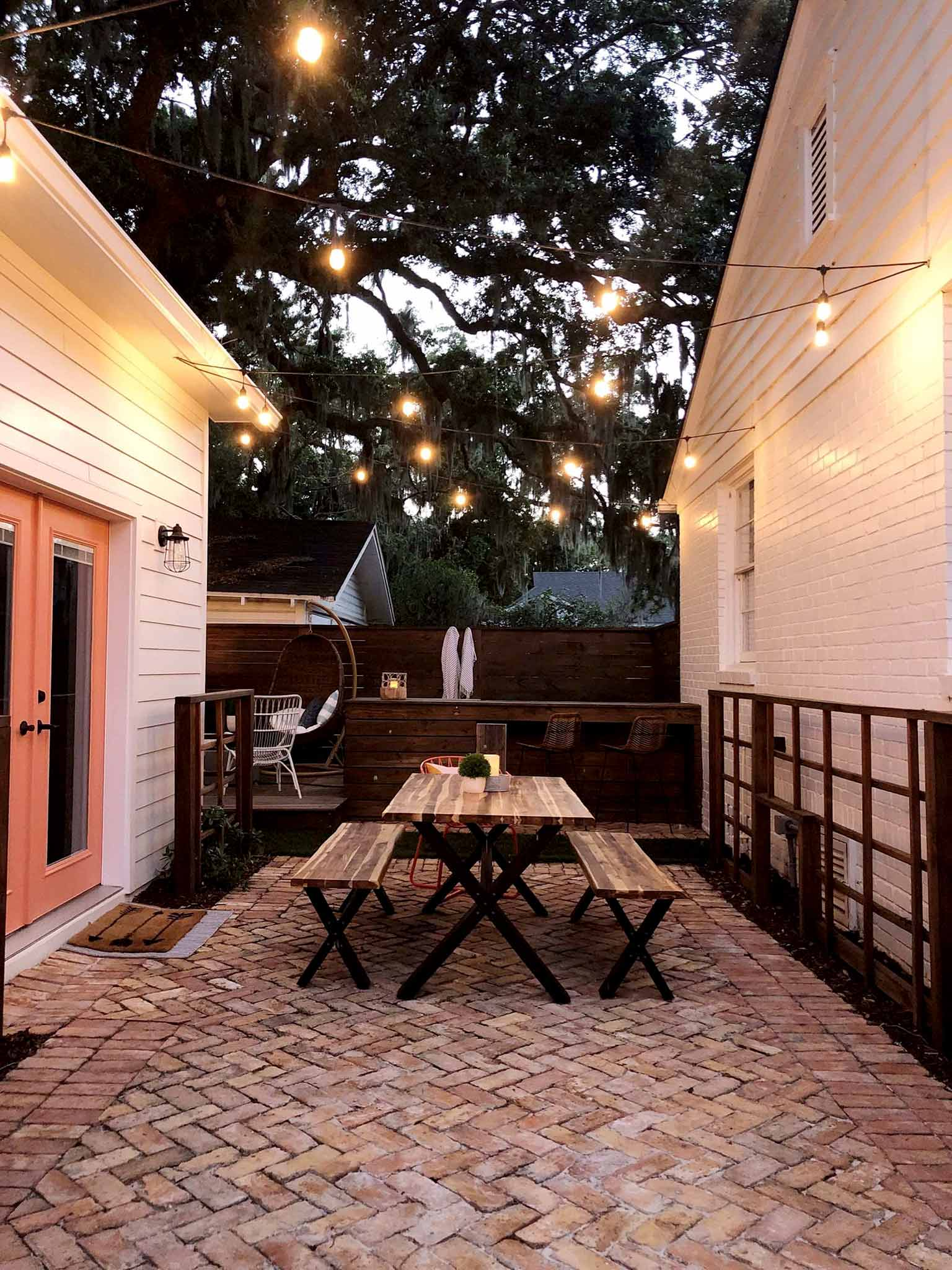 brick patio with table and benches under string lights